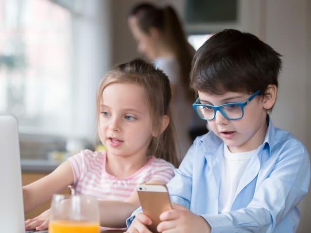 Zwei kleine Kinder mit Handy in der Hand.