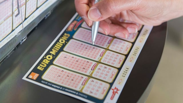 Ein Spieler füllt ein Euro-Millions-Schein aus.