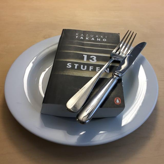 «13 Stufen» von Kazuaki Takano liegt auf einem weissen Teller. Messer und Gabel über das Buch gelegt.