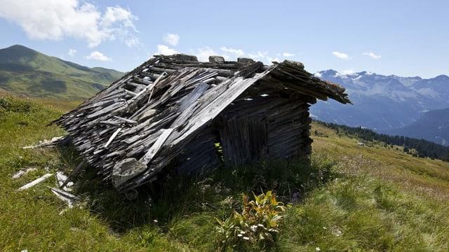 Ein altes Holzgebäude mit einem verfallenen Dach ist abgebildet.