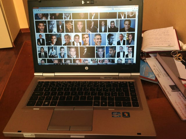 Ein Laptop auf einem Tisch, auf dessen Bildschirm viele Bilder von Schauspieler George Clooney sind.
