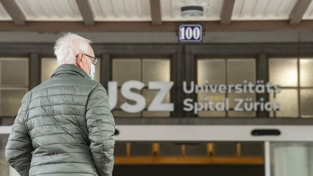 Ein Mann steht vor dem Eingang des Universitätsspital Zürich.