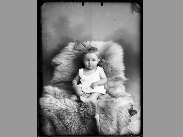 Ein Kind auf einem Stuhl, eingebettet in ein Fell.