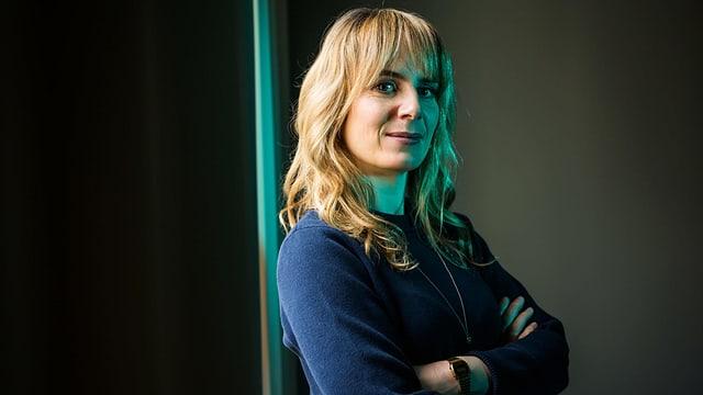 Anna Pieri Zuercher steht an einer Wand. Sie trägt einen blauen Pullover.