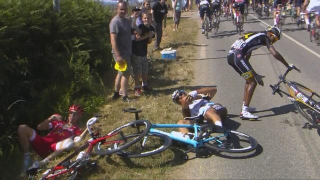 3 Fahrer liegen nach einem Sturz am Boden.