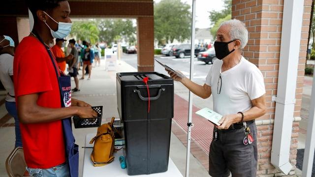Ein Mann wirft seinen Brief auf einem Trottoir in die Urne, ein Wahlhelfer schaut zu.