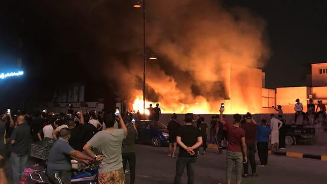 Protestierende stehen vor einem Brand in Bagdad.