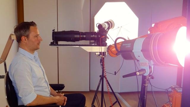 Daniel Wagner sitzt auf einem Stuhl, wird von allen Seiten beleuchtet - vor ihm der Roboterarm mit der darauf montierten Kamera.