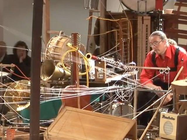 Ein Mann sitzt hinter einem Gebilde aus verschiedenen Instrumenten, die alle mit weissen Schnüren verbunden sind.