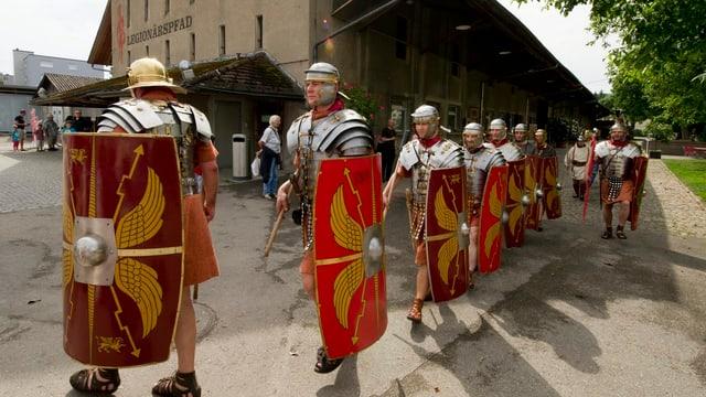 Schauspieler in Legionärsrüstungen mit Schutzschildern