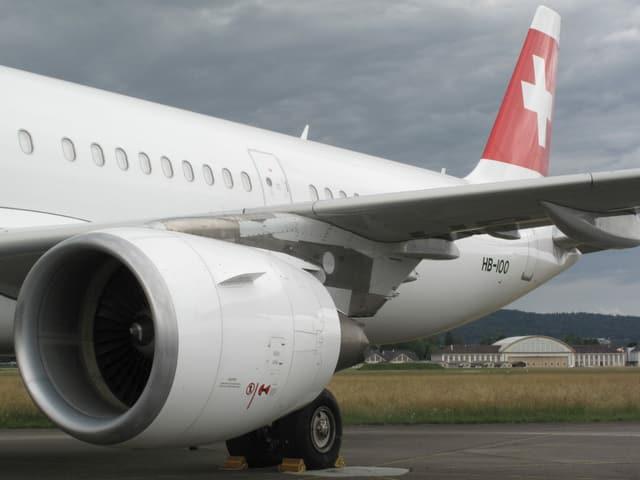 Heck und Triebwerk einer Swissmaschine, im Hintergrund der Hangar von Dübendorf
