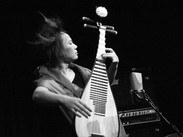 Yang Jing spielt mit wehenden Haaren auf der Pipa.