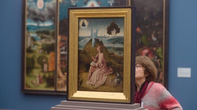 Eine Besucherin wandert durch eine Ausstellung zu Hieronymus Bosch in Berlin.