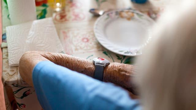 Aufnahme einer alten Frau, die am Tisch vor einem leeren Teller sitzt.