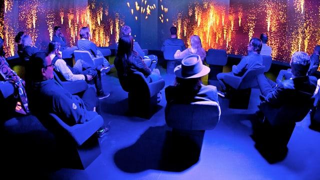 Leute sitzen in einem blau beleuchteten Museumssaal un dsehen sich feurige Animationen an.