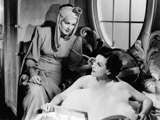 Zwei Frauen: eine sitzt auf einem Stuhl, die andere in der Badewanne.