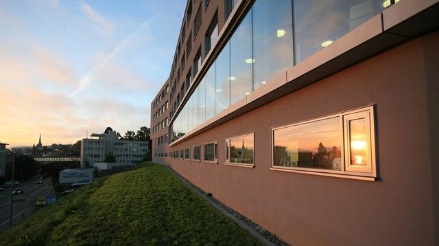 Ein grosses, rotes Haus, in den Fenstern spiegelt sich der Sonnenuntergang.