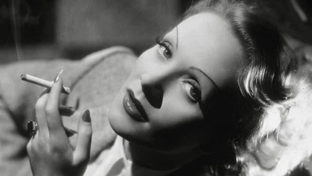Porträt von Marlene Dietrich mit laszivem Blick und Zigarette.