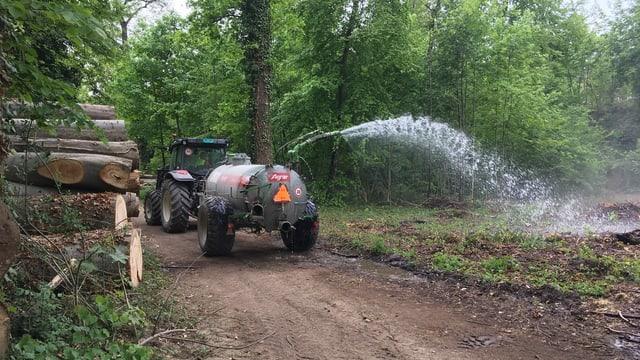 Ein Jauchewagen im Wald bespritzt kleine Bäume mit Wasser.