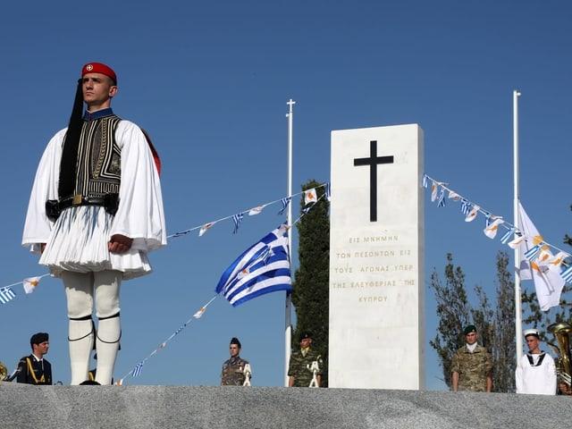 Ein Soldat in Tracht steht vor einem Denkmal.