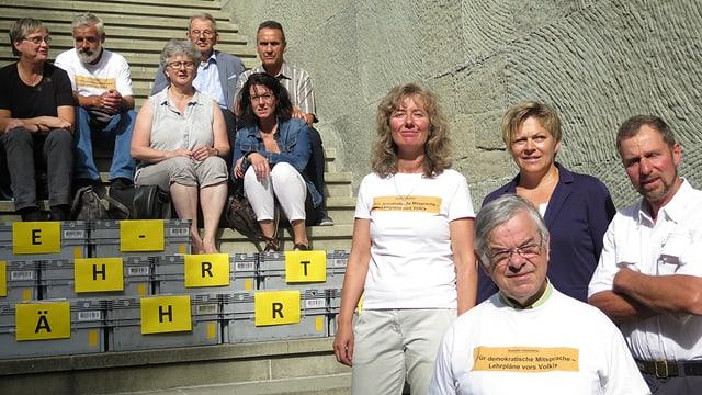 Menschen sitzen vor Kisten auf einer Treppe.