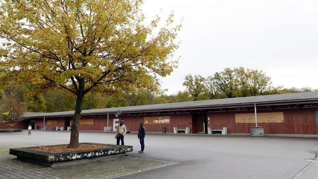 Eine langgezogene Baracke, davor stehen zwei Asylsuchende auf einem Vorplatz