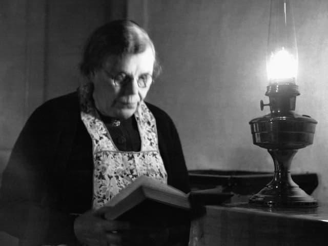 Eine Frau liest. Auf dem Tisch steht eine Kerosinlampe.