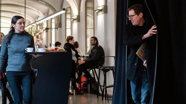 Ein Mann betritt durch einen scharzen Vorhang ein Café, in dem einige Leute sitzen.
