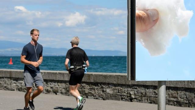 Ein Mann joggt an einem See an einem Plakat vorbei, darauf ein Daumen auf einer Wolke.