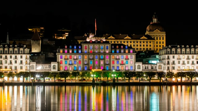 Hotel am See in der Nacht mit farbig beleuchteten Fenstern.