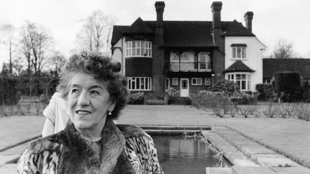Eine Frau im Pelzmantel steht vor einer Villa mit Pool und schaut in den Himmel