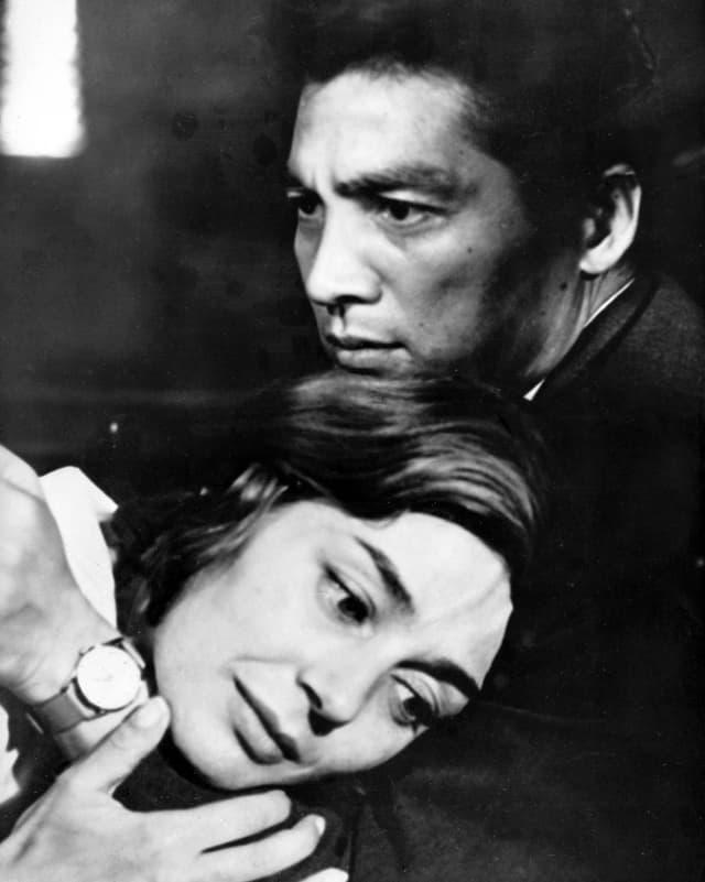 Eine Frau liegt einem Mann in den Armen.