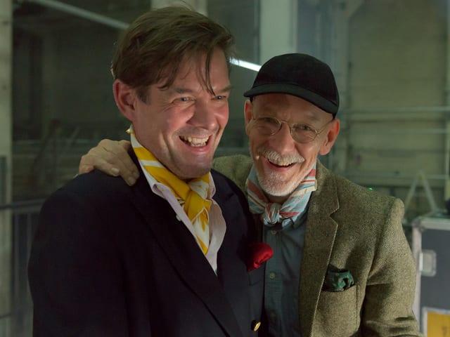 Zwei Männerstehen lachend nebeneinander.