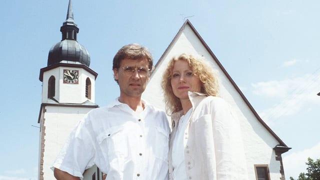 Maren Kroymann und Robert Atzorn stehen vor einem Kirche.
