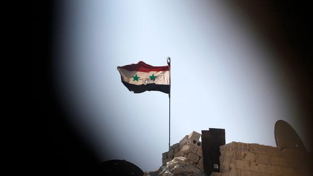Eine syrische Flagge über flattert auf einem von Regierungstruppen kontrollierten Gebäude in Aleppo.