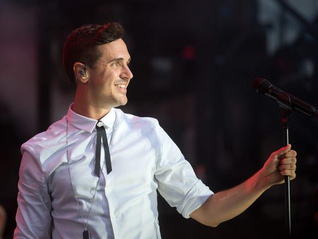 Seven mit weissen Hemd hält das Mikrofon und lächelt Richtung Publikum.