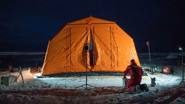 Ein orangefarbenes Ballonzelt steht beleuchtet auf einer Eisscholle.