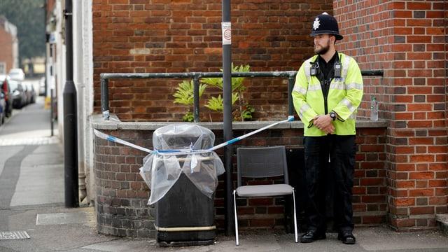 Ein Wachmann steht vor einem versiegelten Abfalleimer