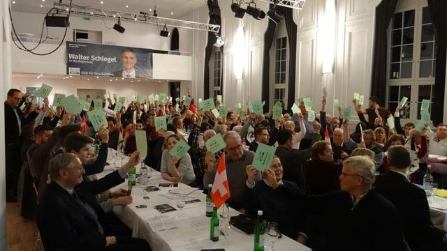 sala plaina cun delegadas e delegads che tegnan ad aut in palpiri verd per vuschar