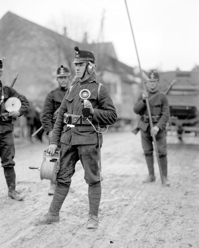 Historisches Bild eines Schweizer Soldaten mit Kabelrolle in der Hand.