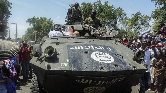 In tanc cun schuldads armads vegn beneventà d'abitants che fan fotografias.