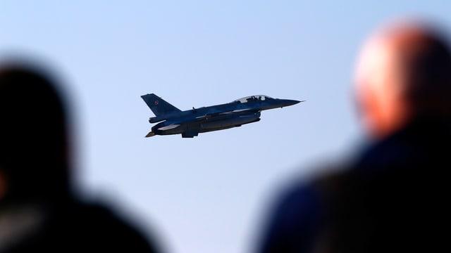 Im Bildmittelpunkt ein Kampfflugzeug in tiefer Flughöhe. An den Bildrändern, im Vordergrund, die verschwommenen Silhouetten von zwei Zuschauern des Militärmanövers Anaconda.