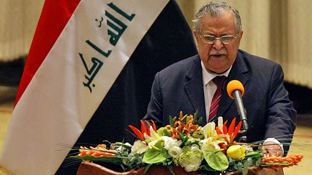 Talabani an Rednerpult. Dahinter irakische Fahne.