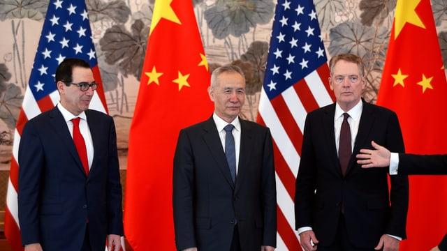Drei Männer vor Fahnen.
