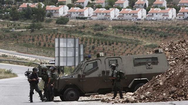 Israelische Soldaten kontrollieren bei einer Strasse.