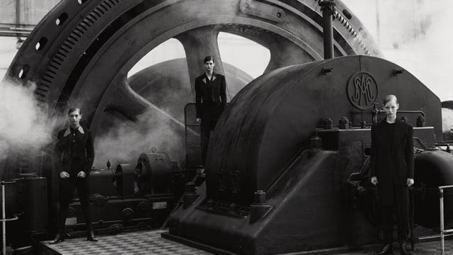 Drei Models posen vor einer Maschinerie.