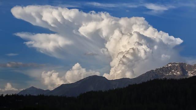 Riesige, weisse Gewitterwolke über den Alpen. Daneben blauer Himmel.