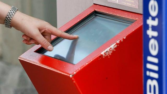 Eine Hand bedient den Touch-Screen eines Billettautomaten