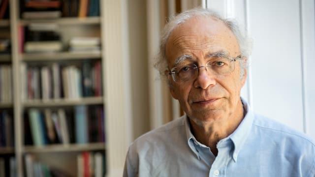 Peter Singer, vor einem Büchergestell stehend, gerade in die Kamera blickend.