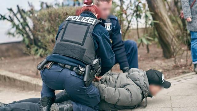 Eine Polizistin und ein Polizist drücken einen Mann auf den Boden und halten seine Arme auf den Rücken.